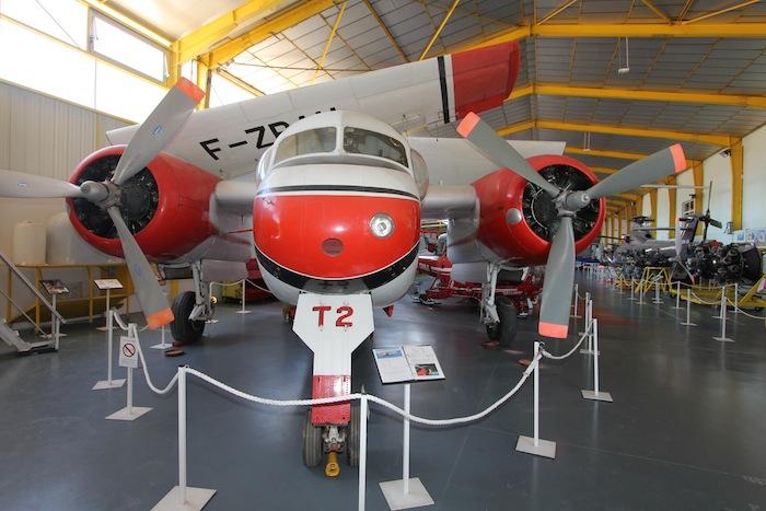 Benjamin du Canadair, le Tracker T2 de la Sécurité Civile dans le hangar, ailes repliées pour rappeler son passé d'avion embarqué.