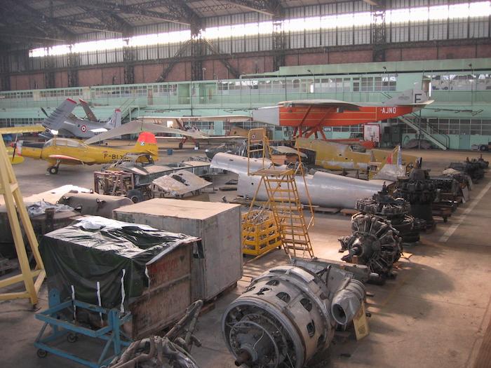 Une collection de moteurs de tous types et d'éléments de divers appareils est entreposée dans le fond de l'immense hangar.